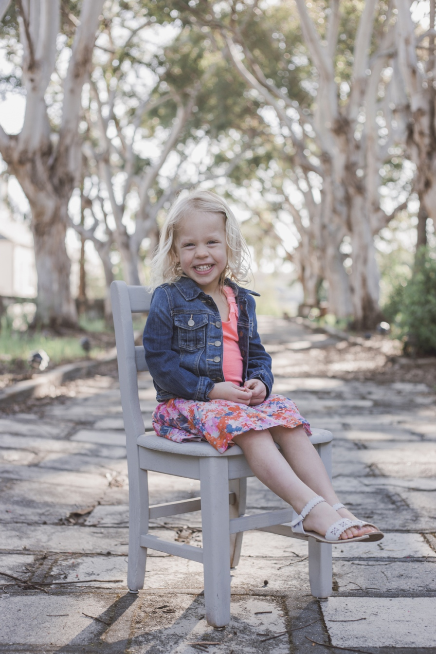image of little girl with big smile outdoors during portrait session by jessica michlle photo