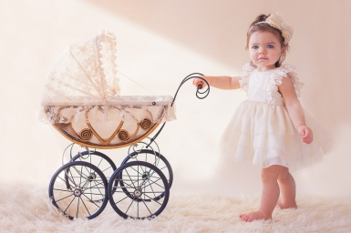 image of one year old baby girl pushing a baby carrage by jessica michelle photo