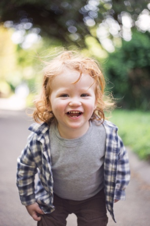 image of redhead toddler boy playing and smiling duing family session by jessica michelle photo