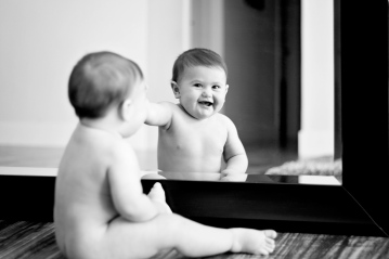 black and white photo of baby girl smiling playing with mirror by jessica michelle photo