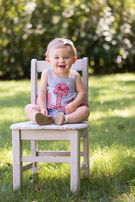 bright image of smiling baby girl on chair during portrait session by jessica michelle photo