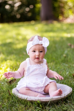 bright image of baby girl wearing white romper by jessica michelle photo port jefferson