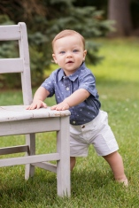 portrait of baby boy with bright blue eyes holding onto chair by jessica michelle photo