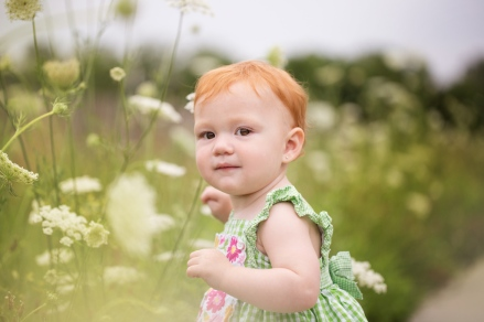 image of redhead baby by white flowers during portrait session by jessica michelle photo