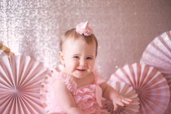 portrait of baby girl in pink birthday hat druing birthday session by jessica michelle photo