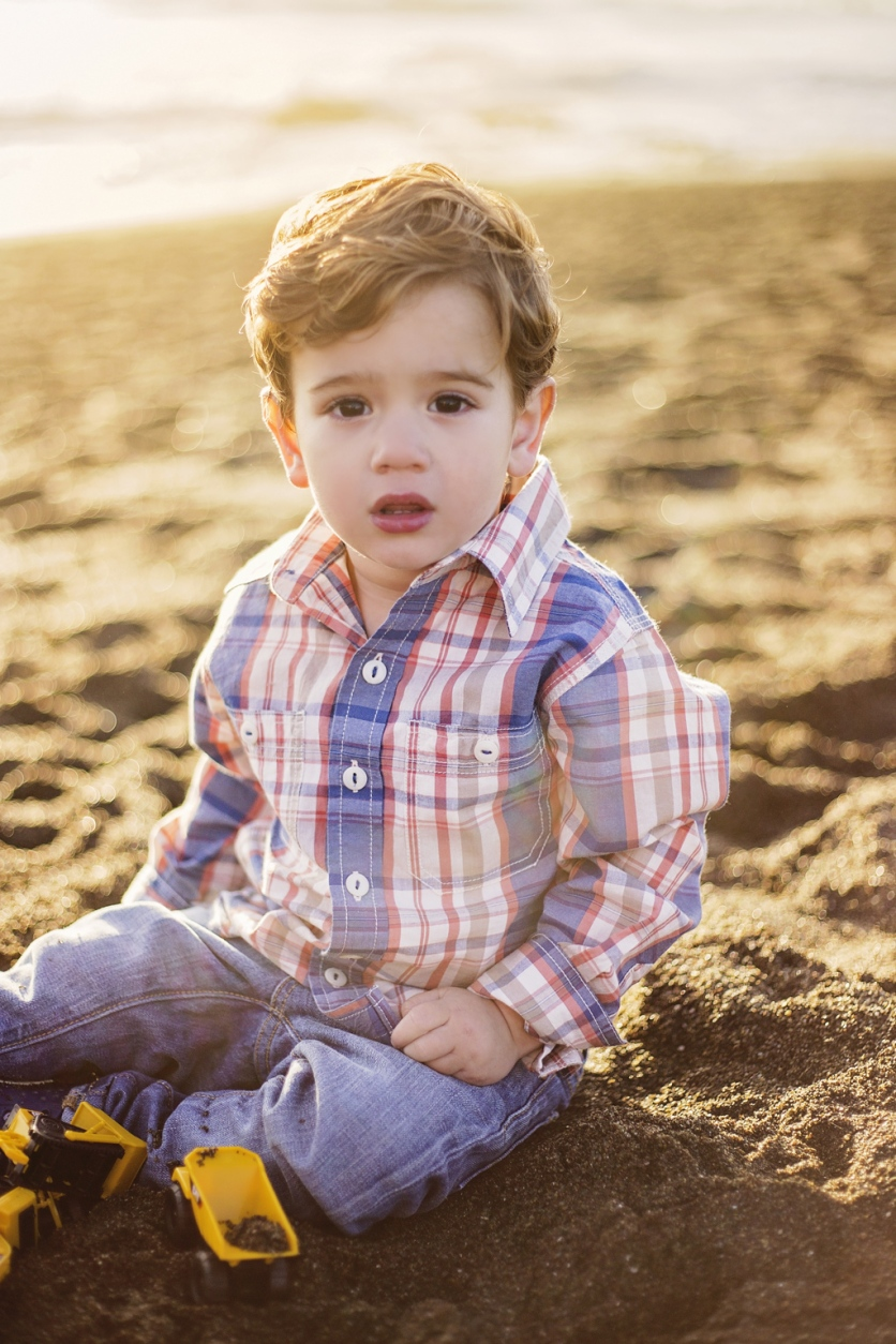 portrait of little boy with trucks on beach by jessica michelle photo