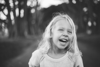 black and white photo of toddler giggling during a family session by jessica michlle photo