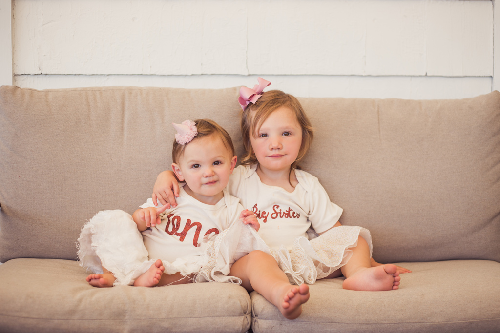 portrait of one year old baby girl with sister at first birthday jessica michelle photo