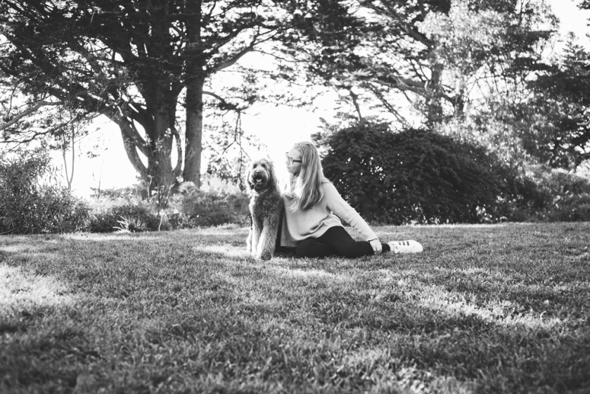 black and white portrait of teen girl and her labradoodle puppy at park by jessica michelle photo